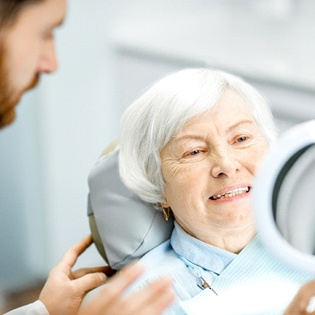 An older woman looking at her smile in the mirror while her dentist stands nearby