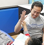 Dr. Tong giving young patient a high five