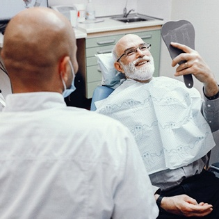 An older man smiling at himself in the mirror while in a dentist chair