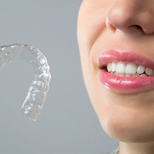 A woman holding an Invisalign aligner