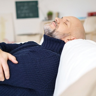 A man wearing a navy sweater and relaxing against the back of the couch after his dental appointment