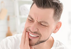 Man grimacing and holding jaw