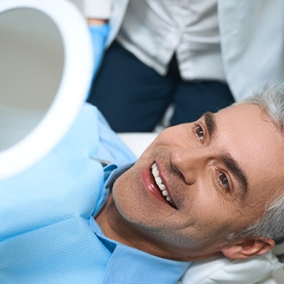 A middle-aged man lying back in a dentist's chair admiring his new and improved smile thanks to cosmetic dentistry