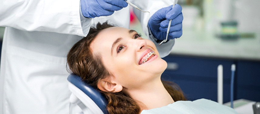 A young woman wearing traditional braces in Tappan and smiling as the orthodontist prepares to check her teeth