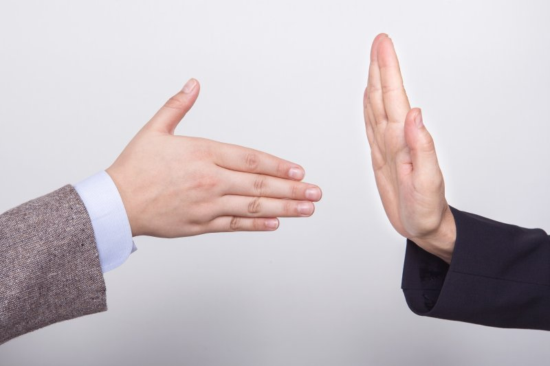 a person trying to shake hands while another puts a hand up to stop them