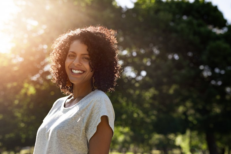 a young woman wearing a gray t-shirt and standing outside, smiling after receiving cosmetic dentistry in Tappan