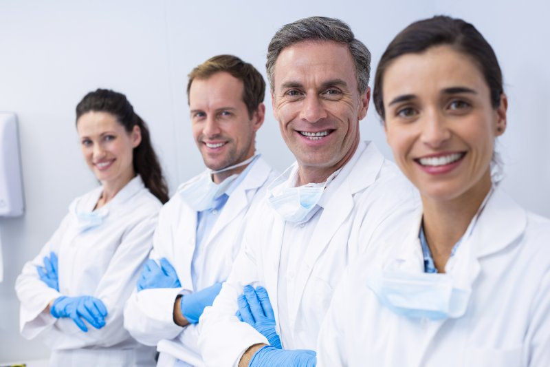 a team of dentists and specialists smiling in preparation for treating dental patients
