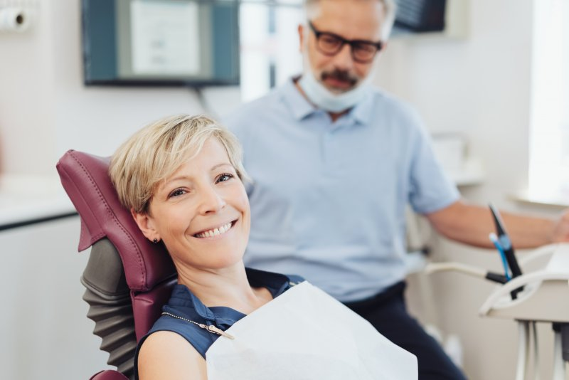 a woman smiling while visiting her dentist for a regular dental checkup in Northvale